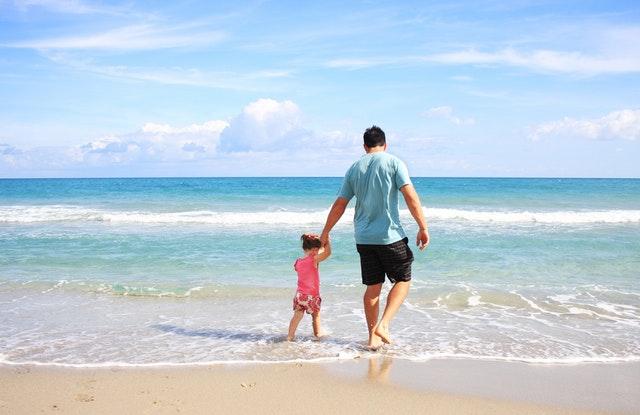 Muž s malým dievčatkom stoja na okraji mora.jpg