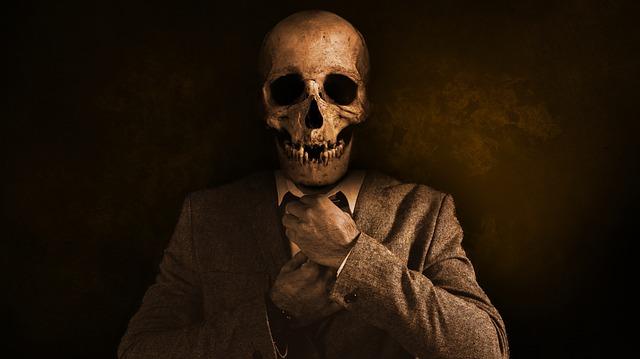 Muž oblečený v obleku s hlavou smrtky