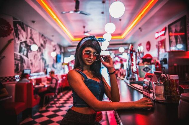 Sexy žena v krátkom džínsovom tričku a v slnečných okuliaroch stojí pri bare