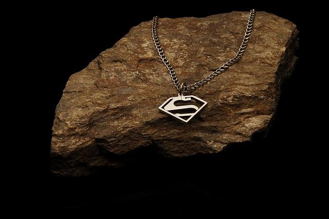 Strieborná retiazka so symbolom Superman zavesená na kameni.jpg