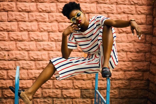 Žena v pásikavom outfite so slnečnými okuliarmi sedí na zábradlí.jpg