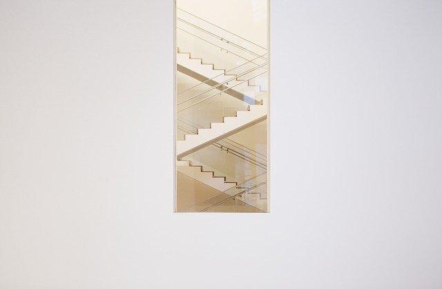 Schodisko so skleneným zábradlím uprostred bielej steny.jpg