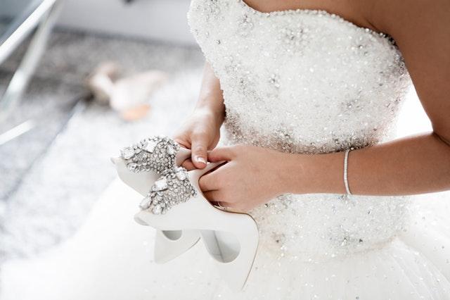 Žena v svadobných šatách rukách drží biele topánky