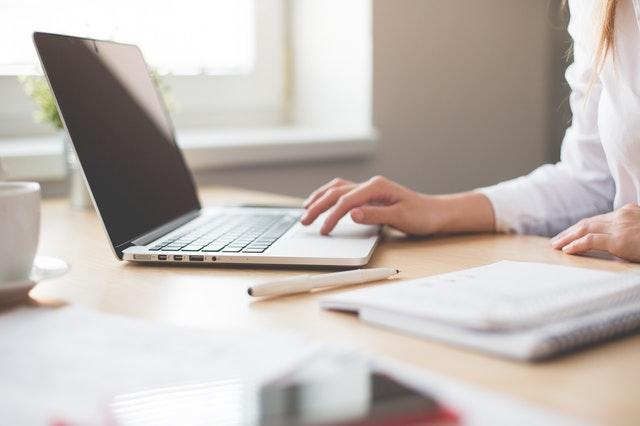 Žena v bielej blúzke sedí pri stole v kancelárii